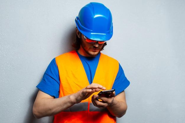 Młody człowiek inżynier pracownik budowlany, pisanie na smartfonie, noszenie sprzętu bezpieczeństwa na szarym tle z teksturą.