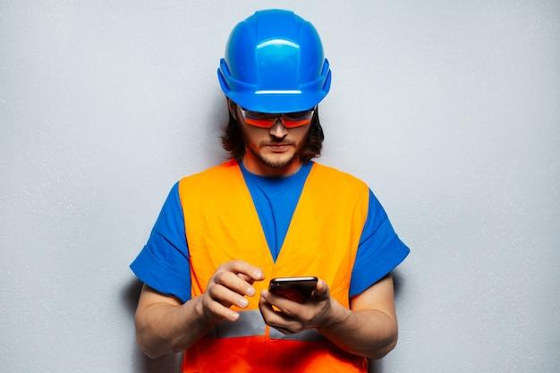 Młody człowiek inżynier pracownik budowlany, za pomocą smartfona, noszenie sprzętu bezpieczeństwa na tle szarej ściany z teksturą.