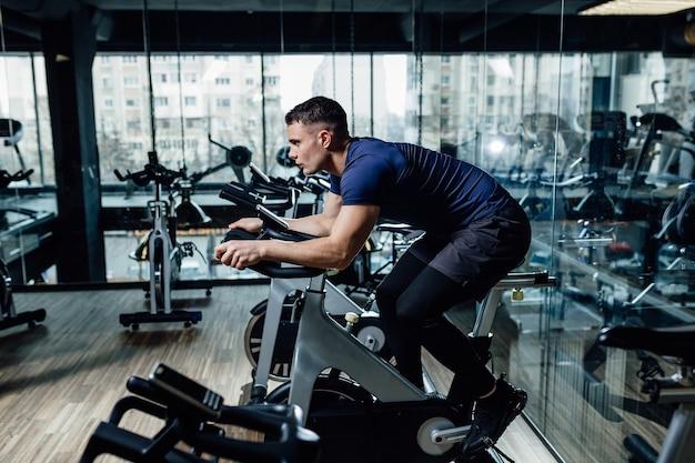 Młody człowiek, jazda na rowerze stacjonarnym. facet ćwiczy na stacjonarnym rowerze.