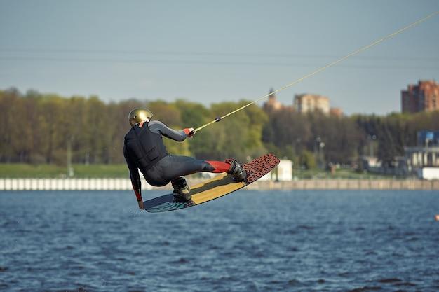 Młody człowiek jazda wakeboard na letnim jeziorze.