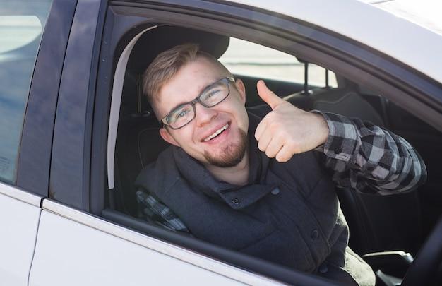Młody człowiek jazdy próbnej nowy samochód i pokazując kciuki do góry