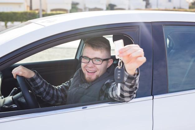 Młody człowiek jazdy próbnej nowy samochód i pokazuje klucz. koncepcja zakupu lub wynajmu samochodu