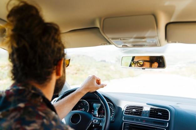 Młody człowiek jazdy samochodem w słoneczny dzień
