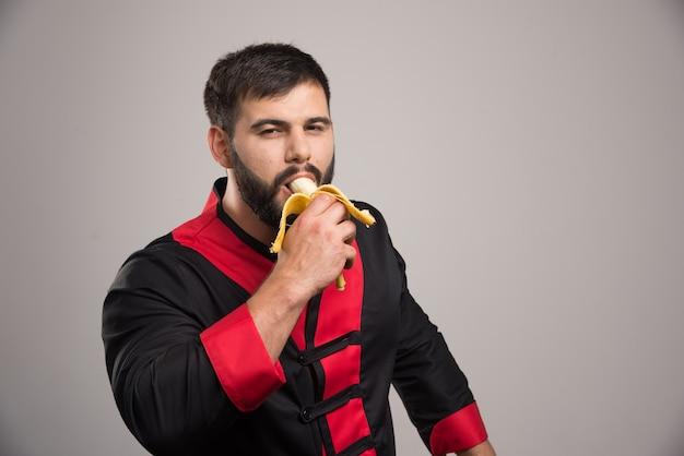 Młody człowiek je banana na szarej ścianie.