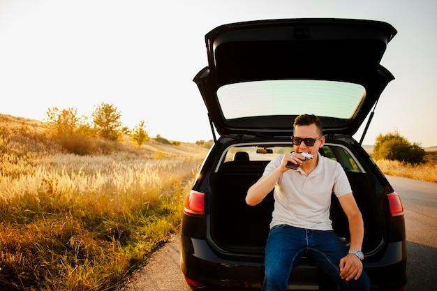 Młody człowiek je czekoladowego baru obsiadanie na bagażniku samochodu