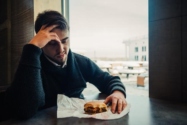 Młody człowiek je hamburger w restauraci