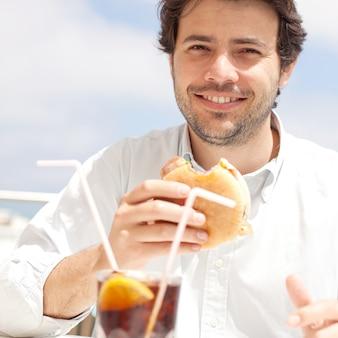 Młody człowiek je hamburguer