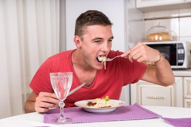 Młody człowiek je talerz spaghetti i mięsa, aby zaspokoić głód, z kieliszkiem białego wina na pierwszym planie