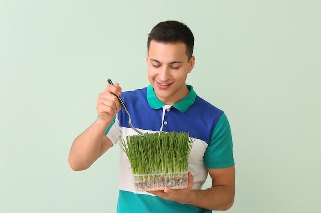Młody człowiek je trawę pszeniczną na kolorowym tle