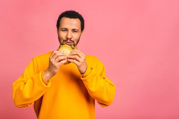 Młody człowiek jedzenie hamburgerów na białym tle nad różowym
