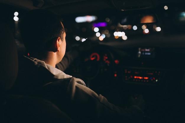 Młody człowiek jedzie jego samochodem w nocy