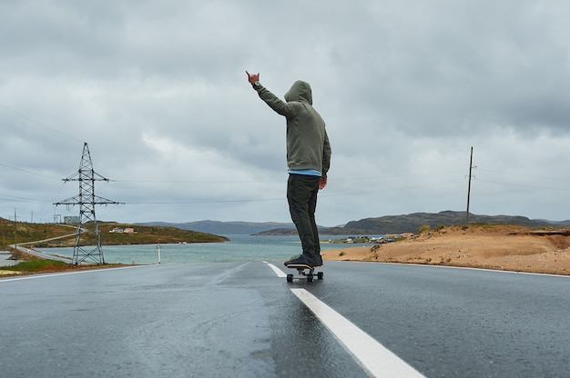 Młody człowiek jedzie longboard na pustej wijącej halnej drodze w lecie, tylni widok.