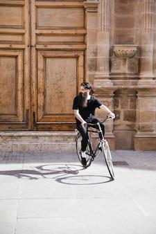 Młody człowiek jedzie rower na ulicie