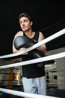 Młody człowiek jest ubranym bokserskie rękawiczki patrzeje daleko od
