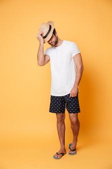 Młody człowiek jest ubranym kapeluszową pozycję odizolowywającą