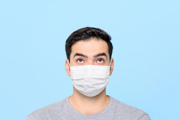 Młody człowiek jest ubranym medycznego twarzy maski główkowanie i patrzeje do pustej przestrzeni nad odosobniony
