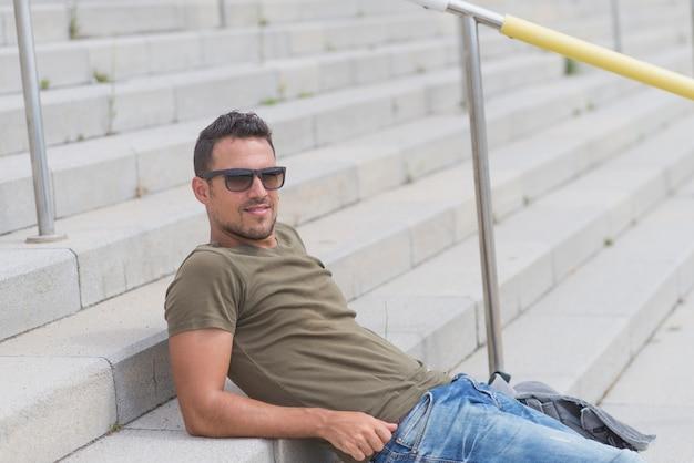 Młody człowiek jest ubranym okulary przeciwsłonecznych siedzi na schodkach