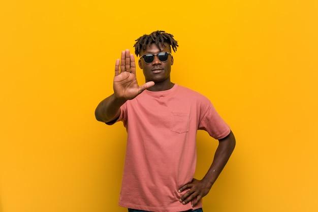 Młody człowiek jest ubranym okulary przeciwsłonecznych stoi z szeroko rozpościerać ręką pokazuje przerwa znaka, zapobiega ciebie