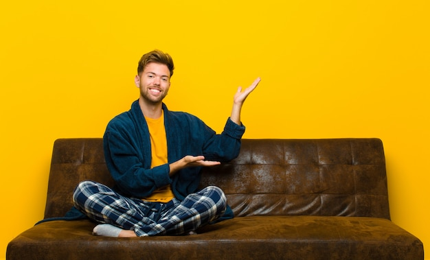 Młody człowiek jest ubranym piżamy ono uśmiecha się dumnie i pewnie czuje się szczęśliwy i zadowolony i pokazuje pojęcie na kopii przestrzeni. siedzieć na kanapie
