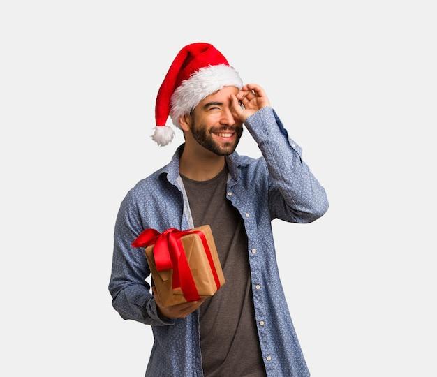 Młody człowiek jest ubranym santa kapelusz robi gestowi spyglass