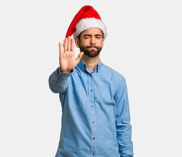 Młody człowiek jest ubranym santa kapeluszu kładzenia rękę z przodem
