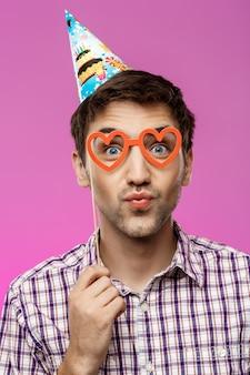 Młody człowiek jest ubranym sfałszowanych szkła nad purpury ścianą. przyjęcie urodzinowe.