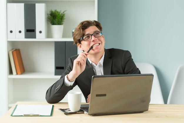 Młody człowiek jest zabawny i entuzjastyczny w pracy w biurze