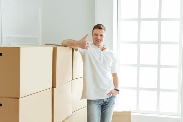 Młody człowiek jest zadowolony z dostawy rzeczy do swojego nowego mieszkania.