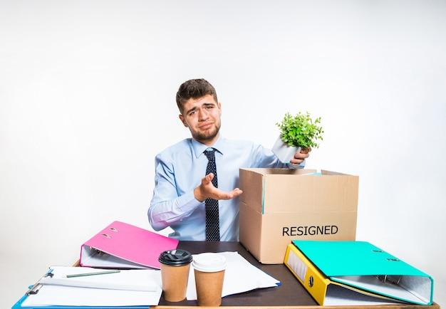 Młody człowiek jest zrezygnowany i składa rzeczy w miejscu pracy, teczki, dokumenty. nie radził sobie z obowiązkami. pojęcie kłopotów pracownika biurowego, biznesu, reklamy, problemów z rezygnacją.