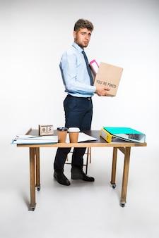 Młody człowiek jest zrezygnowany i składa rzeczy w miejscu pracy