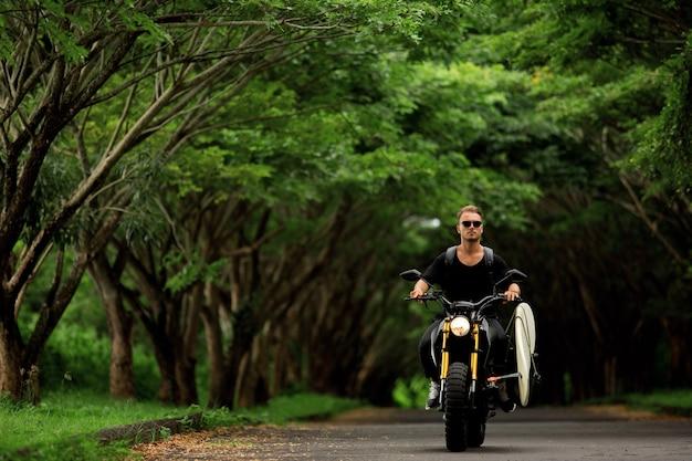 Młody człowiek jeździ motocyklem z deską surfingową