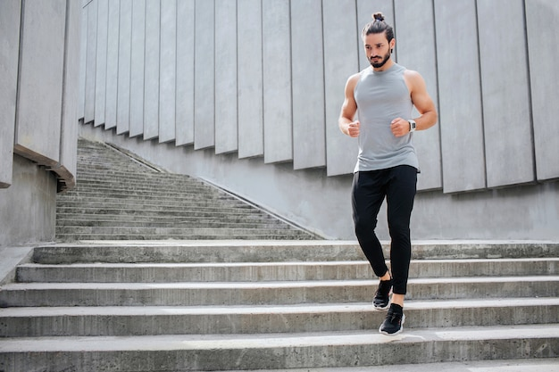 Młody człowiek jogging przy schodach