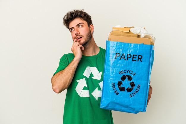 Młody człowiek kaukaski człowiek recyklingu kartonu na białym tle zrelaksowany myślenie o czymś patrząc na miejsce na kopię.