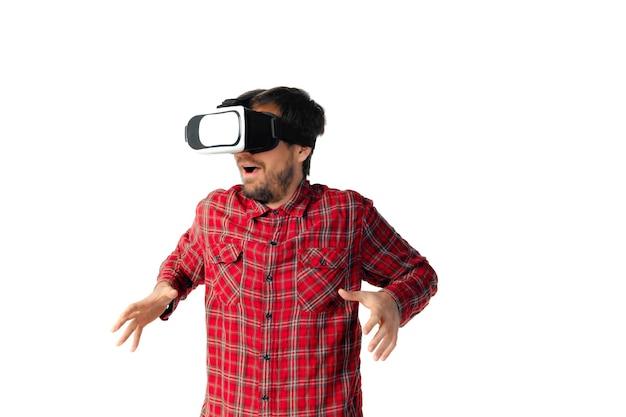 Młody człowiek kaukaski emocjonalne gry, za pomocą zestawu słuchawkowego wirtualnej rzeczywistości na białym tle na tle białego studia. pojęcie nowoczesnych technologii, gadżetów, technologii, ludzkich emocji, reklamy. miejsce. ar, vr.
