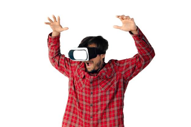 Młody człowiek kaukaski emocjonalne gry, za pomocą zestawu słuchawkowego wirtualnej rzeczywistości na białym tle.