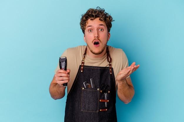 Młody człowiek kaukaski fryzjer na białym tle na niebieskiej ścianie zaskoczony i zszokowany