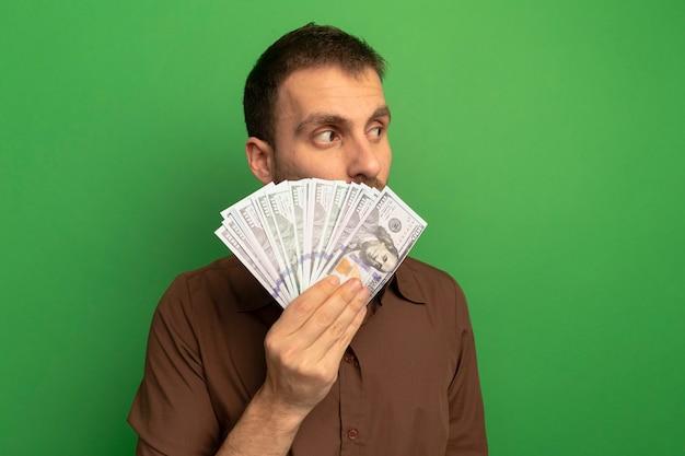 Młody człowiek kaukaski gospodarstwa pieniądze patrząc z boku z tyłu na białym tle na zielonym tle z miejsca na kopię