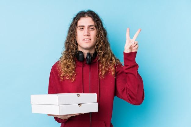 Młody człowiek kaukaski gospodarstwa pizze na białym tle wyświetlono numer dwa palcami.