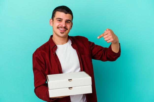 Młody człowiek kaukaski gospodarstwa pizze na białym tle
