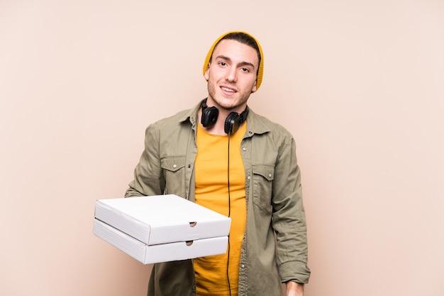 Młody człowiek kaukaski gospodarstwa pizze szczęśliwy, uśmiechnięty i wesoły.