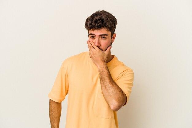 Młody człowiek kaukaski na białym tle na białym tle obejmujące usta rękami patrząc zmartwiony.