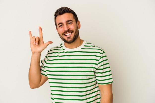 Młody człowiek kaukaski na białym tle na białym tle przedstawiający gest rogów jako koncepcja rewolucji.
