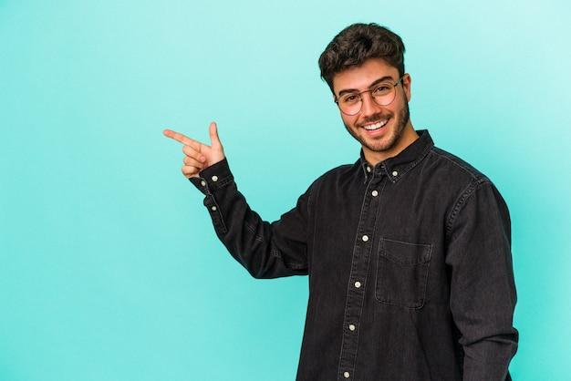Młody człowiek kaukaski na białym tle na niebieskim tle uśmiechając się radośnie wskazując palcem wskazującym od.