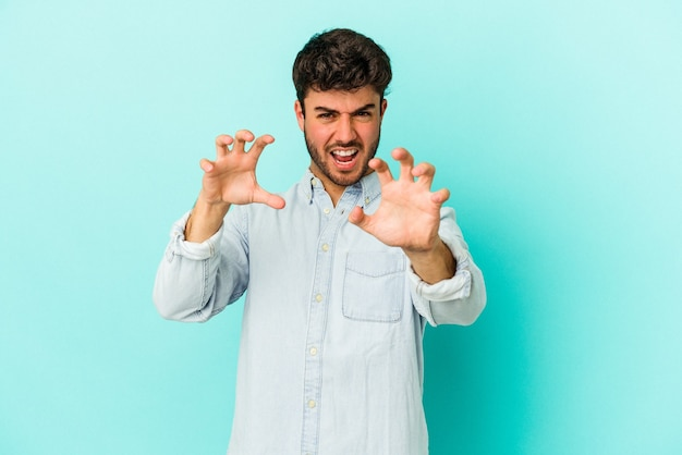 Młody człowiek kaukaski na białym tle na niebieskim tle zdenerwowany krzyczy z napiętymi rękami.