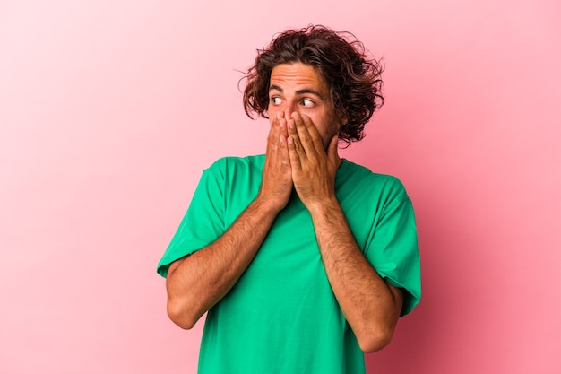 Młody człowiek kaukaski na białym tle na różowy bakcground miło patrząc na miejsce obejmujące usta ręką.