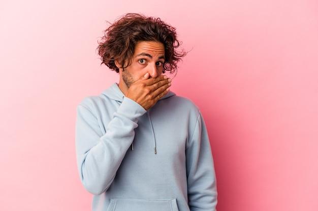 Młody człowiek kaukaski na białym tle na różowy bakcground obejmujące usta rękami patrząc zmartwiony.