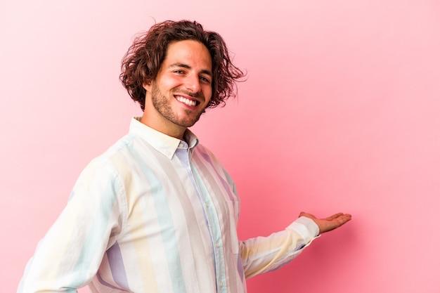 Młody człowiek kaukaski na białym tle na różowym bakcground pokazujący mile widziane wyrażenie.