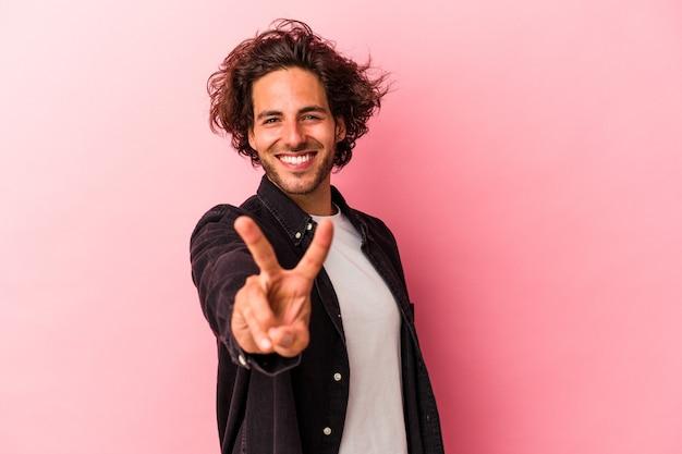 Młody człowiek kaukaski na białym tle na różowym bakcground radosny i beztroski pokazując symbol pokoju palcami.