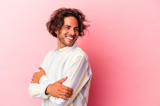 Młody człowiek kaukaski na białym tle na różowym bakcground śmiejąc się i zabawę.