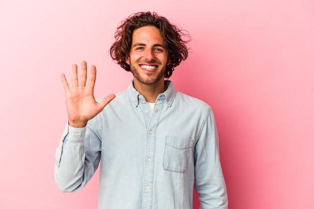 Młody człowiek kaukaski na białym tle na różowym bakcground uśmiechnięty wesoły wyświetlono numer pięć palcami.
